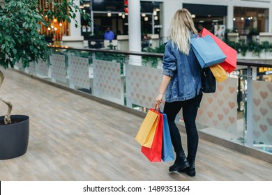Commerce and shopping season. Woman in a denim jacket with bags on blurred shopping mall background. Back to the camera. The face is not visible. Shopping, sale concept, copy space on left side