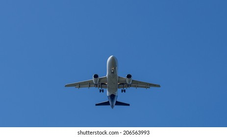 Commercial 2 engine jet plane leading into landing on a blue sky