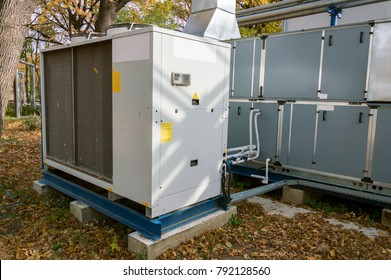 Commercial air handling unit with big condensing unit standing outdoor on the ground covered by fallen leaves