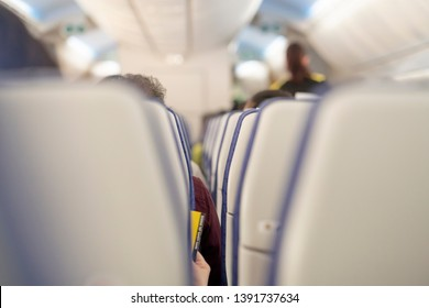 Commercial aircraft cabin behind rows of seats with full of passengers. Morning light in the salon of the airliner. economy class