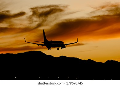 Commercial aircraft land at an airport at sunset