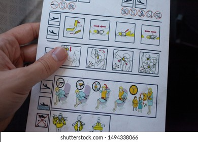 Commercial aircraft safety briefing card, being held by a passenger whilst reading. Showing emergency positions in case of an aircraft emergency onboard.