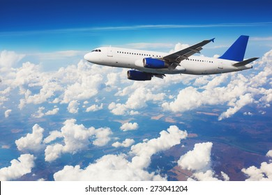 Commercial airliner flying above clouds with blue sky in background.