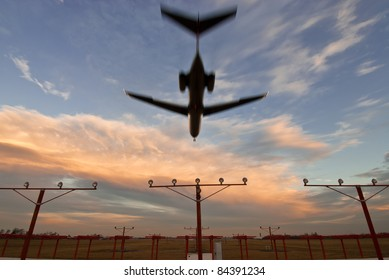 Commercial airliner landing at dusk from end of runway