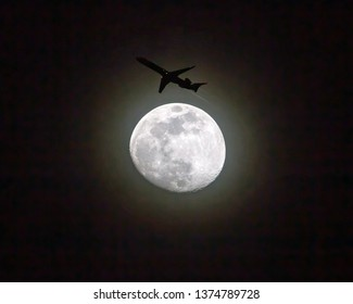 A commercial airliner at low altitude passes by a full moon at night.