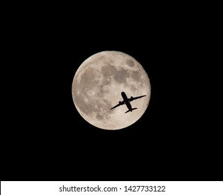 A commercial airliner passes in front of a full moon shortly after takeoff.