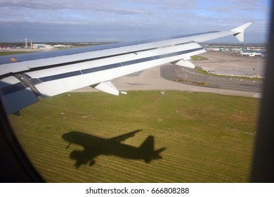 Commercial airplane about to land at arrival airport - view of the wing and the shadow of the plane