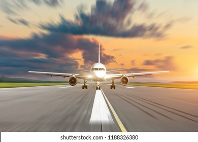 Commercial airplane accelerates on runway airport at sunset at a speed motion blur