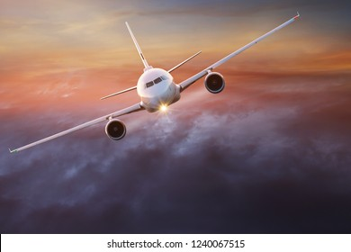 Commercial airplane flying above dramatic clouds during sunset.
