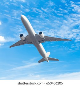 commercial airplane flying against blue sky background with clipping path