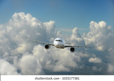 Commercial airplane flying over the clouds and blue skies as background