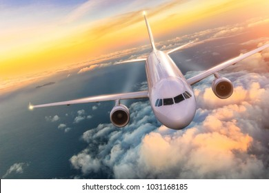 Commercial airplane jetliner flying above clouds in beautiful sunset light. Concept of travel and business.