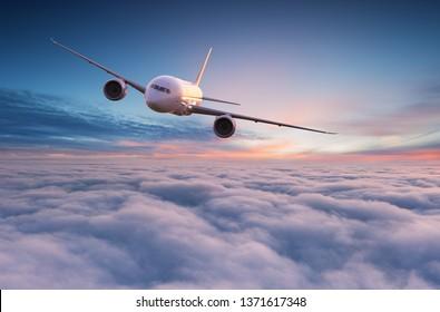 Gewerblicher Jetliner, der bei schönem Sonnenuntergang über dramatischen Wolken fliegt. Reisekonzept.