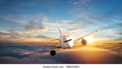 Commercial airplane jetliner flying above clouds in beautiful sunset light. Travel and business concept