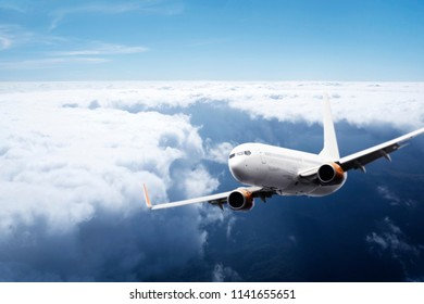 Commercial Airplane jumbo jet flying past clouds in a blue sky. Concept travel business transport airliner.