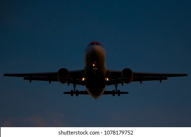 Commercial airplane landing at dusk. Front towards camera. Beacon and navigation lights on. Flaps and gear down. Dark sky.