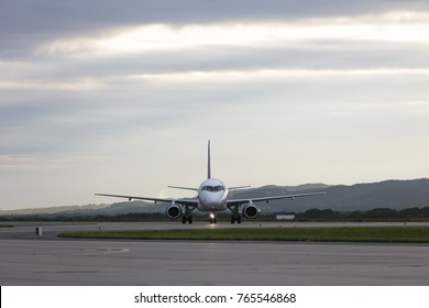 Commercial airplane parking at the airport on evening sky background