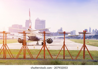 Commercial airplane preparing for take-off at London City Airport with Canary Wharf in the background