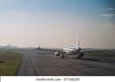 Commercial airplane queue and taxiing on tarmac to take off on runway on a morning