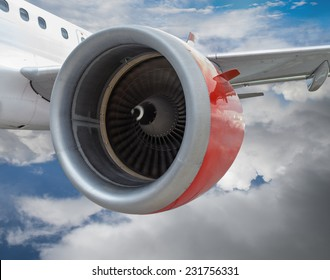 Commercial airplane with red engine in flight through clouds. Realistic engine spinning motion on close up.