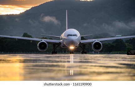 The commercial airplane standing on the airport taxiway or apron at sunset with blue sky background. Passenger airplane landing or taking off. Airplane concept.
