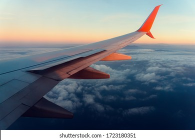 Commercial airplane wing with orange winglet shot form illuminator on high altitude on dawn. Wide angle shot with visible clouds under the plane