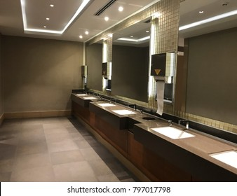 Commercial bathroom. Interiors shots of a modern bathroom in the foreground the glass counter top washbasin and the big mirror