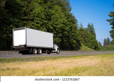 Commercial big rig day cab local haul white semi truck transporting dry van box trailer on the green highway road with trees for delivery of industrial cargo to warehouse or local business