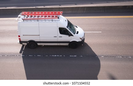 Commercial cargo mini van with long leaders on the roof running on the road to point of service or place of construction business