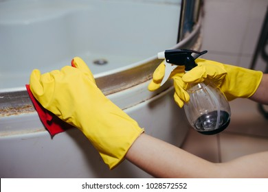 Commercial cleaning. Employee hand in rubber protective glove with micro fiber cloth washing a ceramic tiles from dust in the bathroom.