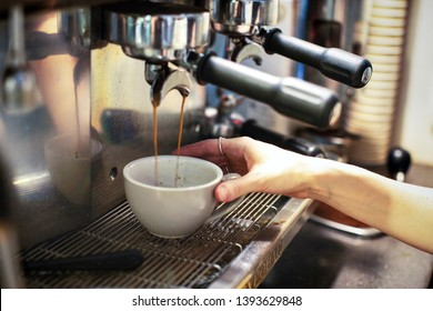 Commercial coffee machine making coffee by barista