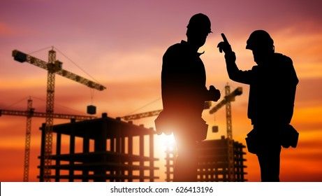 Commercial Construction Concept with Silhouette of Two Workers Wearing Hard Hats and Construction Site in the Background.