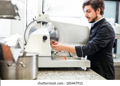 Commercial cook or chef slicing cold meat on a large rotary cutter in restaurant or hotel while preparing ingredients for the evening meal