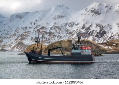 Commercial crab boat traveling with snowy mountainous background in Alaska
