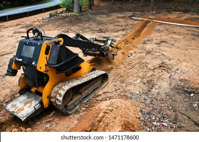 A commercial ditch digging machine cutting a trench in yard to install pipe for a new sprinkler system