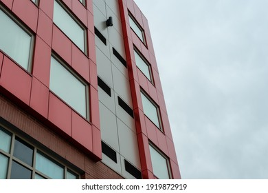 Commercial external metal composite panels on a building with blue sky and clouds in the background. The durable metal composite panels are both red and grey in colour on the modern building.