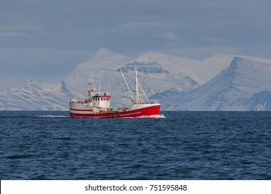 Commercial fishing boat in Icelandic waters with snowy mountains in the background.