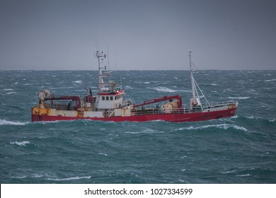 Commercial fishing boat sailing near southwest coast of Iceland.