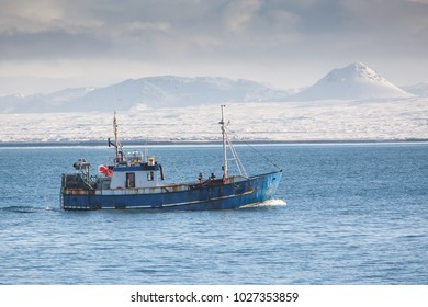 Commercial fishing boat with snowy mountains in background.