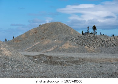 A commercial gravel pit of crushed stone, sand and aggregate for construction.  The stones are of different sizes and in large mounds.  There's trees in the background under a blue sky with clouds.