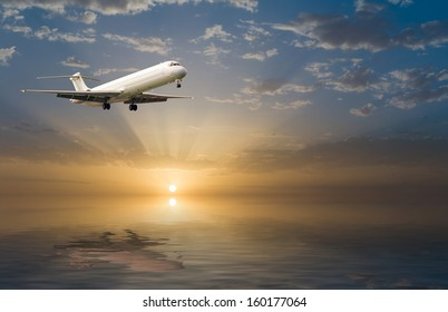 commercial jet airplane in flight at sunset above the sea