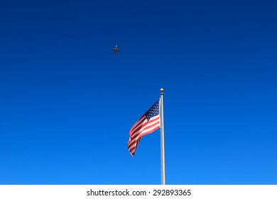 Commercial jet airplane flying in the sky over the American flag.