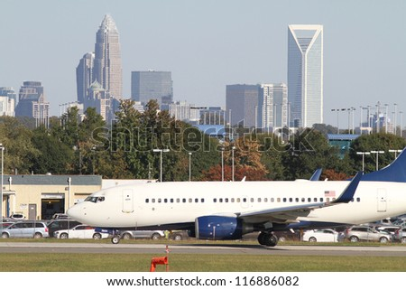 Commercial jet on an airport runway with city skyline in the background.