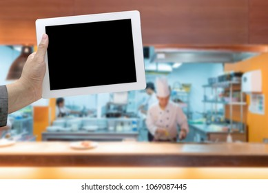 Commercial Kitchen Blurred  and chef cooking Background with hand hold digital tablet