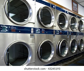 Commercial Laundromat wall of front loading industrial washing machines .