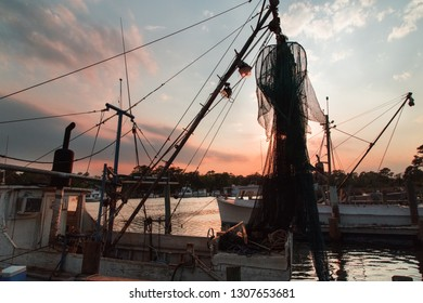 Commercial little fishing boats in harbor.  Boat silhouette. Picturesque  sunset on river. NC.USA.