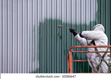 A commercial painter on an industrial lift spray painting a steel exterior wall or duct.