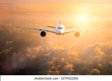 Commercial passenger aircraft flying above dramatic clouds in colourful sunset sky background. Transportation or travel concept.