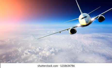Commercial passenger airplane flying above the clouds at sunset