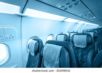 Commercial passengers airplane interior. Blue toned